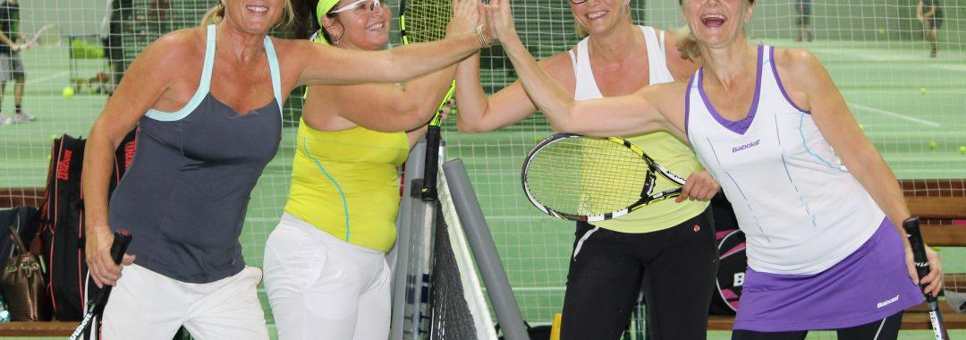 Vier Damen schlagen die Hände nach einem Tennismatch zusammen