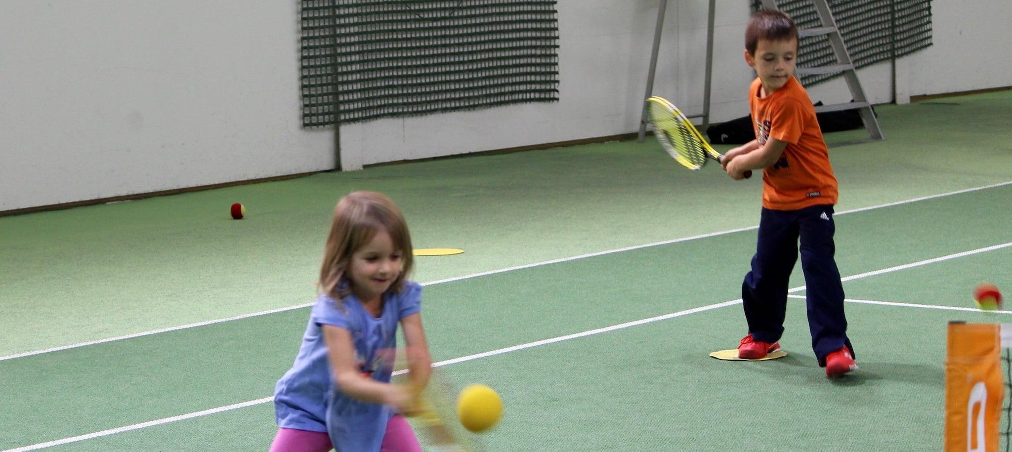 Kleine Kindern beim Tennis spielen