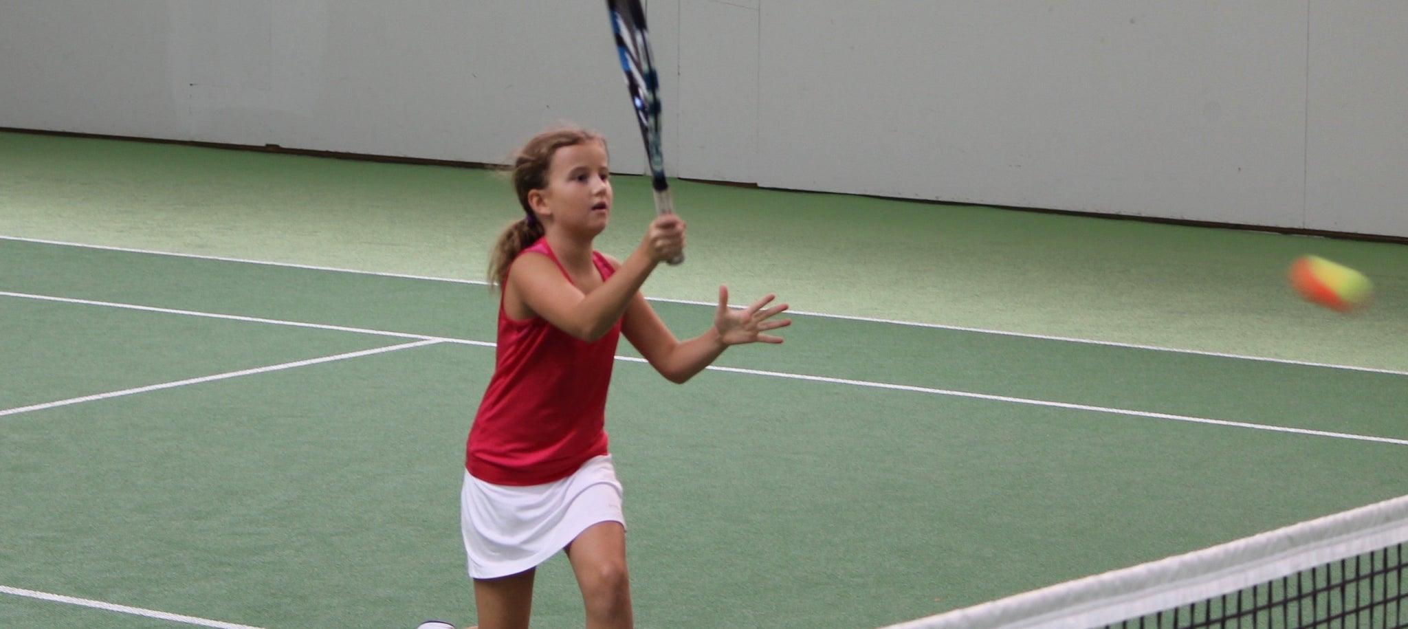 Mädchen kurz bevor es den Tennisball trifft